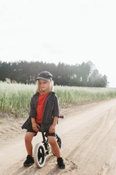Stylish toddler boy with long blonde hair sitting on balance bike on a country road. Backlit portrait.