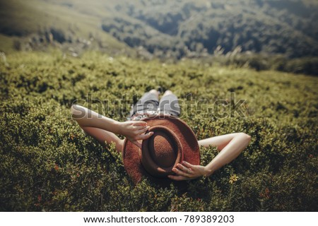stylish traveler woman in hat lying on grass and relaxing in mountains. hipster girl on top of mountain, resting, hat on her face. space for text. atmospheric moment. wanderlust and travel concept. Foto stock ©