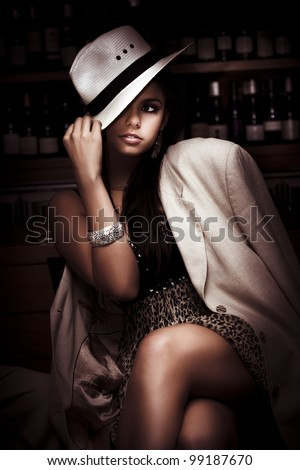 Stylish Trendy And Fashionable Female Model Wearing Slanting Hat And Coat Over A Elegant Evening Dress Inside A Dark Bar In A Depiction Of Dark Fashion