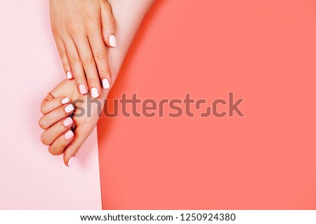Stylish trendy female manicure. Beautiful young woman's hands on Living Coral background. Color of the year 2019 concept.