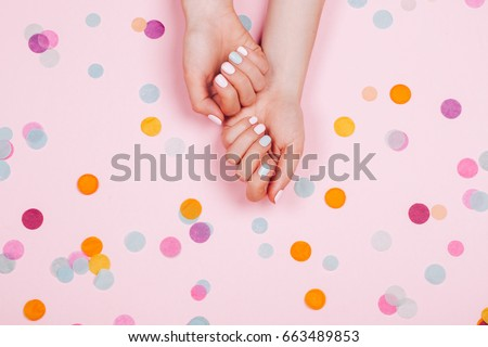 Stylish trendy female pink and blue manicure. Beautiful young woman's hands on pink pastel background with festive multicolored confetti. #663489853