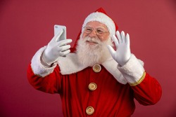 Stylish trendy grandfather aged mature Santa tradition winter costume headwear spectacles white beard take christmastime selfie picture front camera in red background.