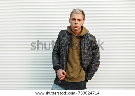 Stylish trendy man in a trendy military jacket with hoodie posing near white metal wall #733024714