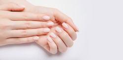 Stylish trendy nail young woman hands pink manicure on white background.