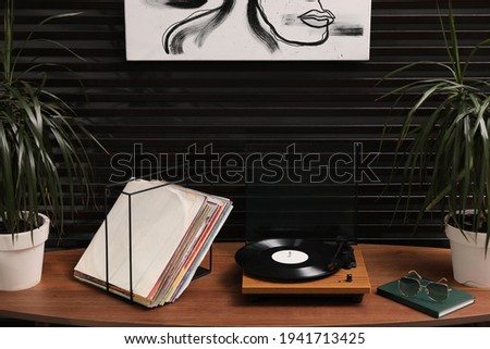 Stylish turntable with vinyl discs on table in room Foto stock ©
