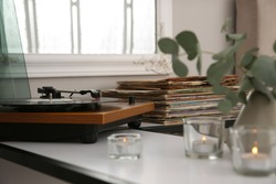 Stylish turntable with vinyl record on table indoors