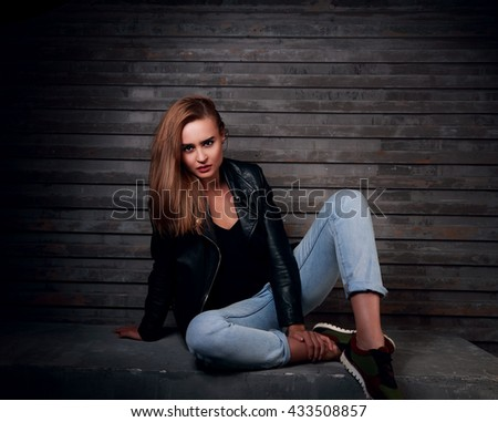 Stylish urban woman sitting on the stone in black jacket and blue jeans with expressive face on wall dark background #433508857