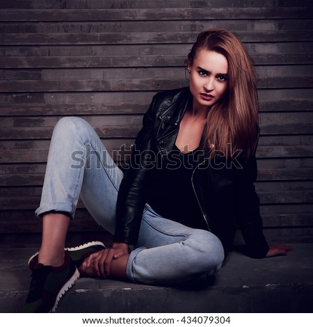 Stylish urban woman sitting on the stone in black jacket and blue jeans with expressive face on wall dark background. Contrast toned portrait #434079304