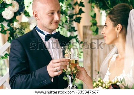 Stylish wedding couple clang glasses after the ceremony