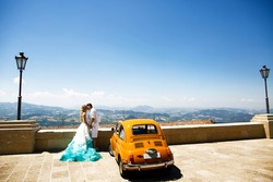 Stylish wedding couple kisses before yellow retro Fiat 500 with great view on mountains behind them