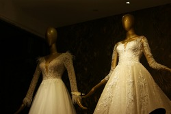 Stylish wedding dresses on mannequins. Mannequins in luxury wedding dresses, dark background. Wedding fashion exhibition.
