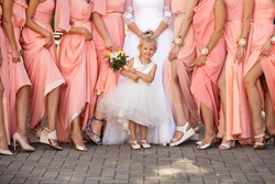 Stylish wedding, little girl- bride's sister holding wedding bouquet near legs of bridesmaids. Colorful, pink or peach same dresses of wedding guests