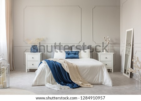Stylish white, grey and petrol blue bedroom design, copy space on empty wall