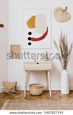 Stylish white interior of living room with mock up poster frame, rattan accessories, leaf, wooden shelf, vase with flowers and elegant personal stuff. Minimalistic concept of home decor. Template.