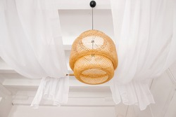 stylish wicker wooden chandelier in boho and Bali style hangs on the ceiling near a white canopy made of weightless tulle. Part of the light airy interior.