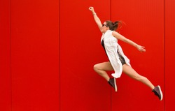 Stylish woman dancing and jumping on a street against a red wall