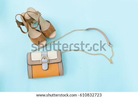 Stylish woman Handbag and shoes on blue background