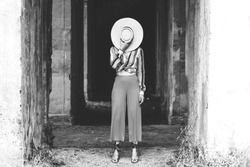 Stylish woman hides her face behind a straw hat. Trend creative brash concept. Monochrome image. Glossy vogue background
