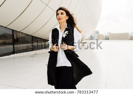 stylish woman in a black suit posing against the background of an unusual building in the city of Baku