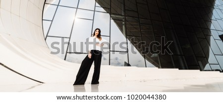 stylish woman in a white shirt posing in the city of Baku