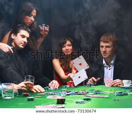 Stylish woman in black suit folds two cards in casino poker at Las Vegas over black