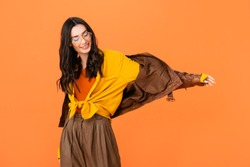 stylish woman in glasses and leather jacket standing with outstretched hand isolated on orange
