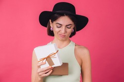 Stylish woman in hat on pink red background isolated space open gift box with unhappy sad face