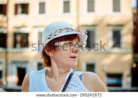 Stylish woman in hat to go in a Rome street