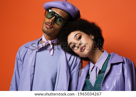 stylish woman in purple jacket leaning on man in beret and sunglasses isolated on orange Сток-фото ©