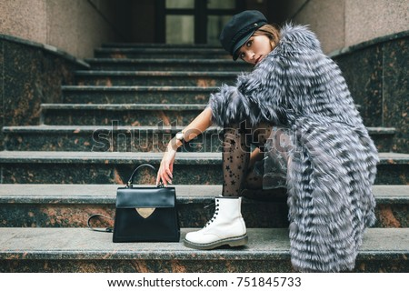 stylish woman in rich fur coat in city street, autumn fashion trend, black leather purse, cap, white boots, urban style, accessories, legs, footwear