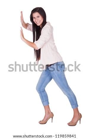 Stylish woman in stilettos and jeans posing in a pushing position isolated on white