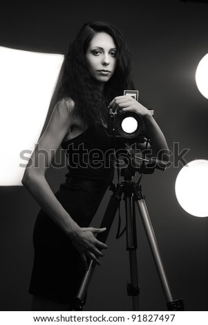 Stylish woman photographer in studio with light accessories on background. Black and white