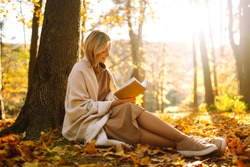 Stylish woman reading a book in the autumn park. Relaxation, enjoying, solitude with nature.
