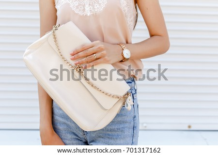 Stylish woman's outfit. Beige cami silk top, blue denim jeans, clutch bag, gold watch and rings against white street wall. Trendy casual outfit. Street fashion. Details of everyday look.