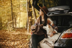 Stylish woman traveller with backpack sitting with cute dog in car trunk in sunny autumn woods. Young hipster female traveling with swiss shepherd white dog. Travel and road trip with pet