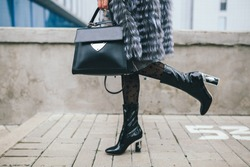 stylish woman walking in city in fur coat, urban street style, winter fashion trend, legs close up, accessories, boots