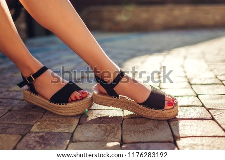 Photo of  Stylish woman wearing black summer shoes with straw sole outdoors. Comfortable sandals. Beauty fashion.