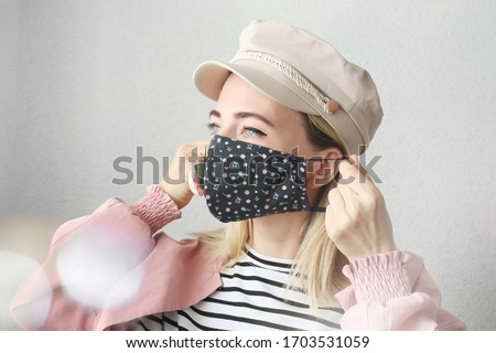 Stylish woman wearing designer  cloth cotton face mask with flower protect against coronavirus.  Reusable fashionable face mask.
