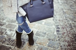 Stylish woman with crossed legs in blue jeans and big leather dark blue bag in hand. Winter fashion outfit