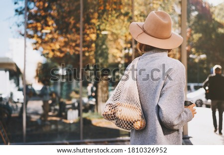 Stylish woman with purchase in cotton reusable net bag and glass cup on storefront background of zero waste shop. Low waste, plastic free lifestyle concept. Eco mesh shopper outdoors with copy space. Photo stock ©