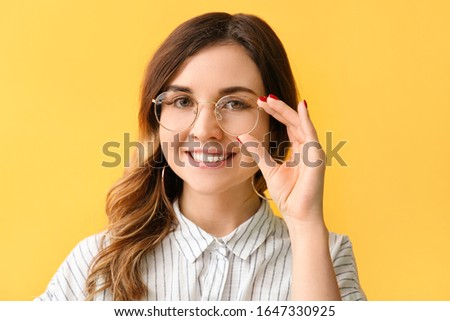 Stylish woman with stylish eyeglasses on color background