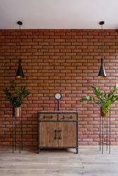 Stylish wooden dresser, two plants in gold pots and two elegant ceiling lamps in room with red brick wall