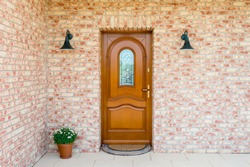 Stylish wooden front door in a detached house - embedded in a brick wall - entrance of a home