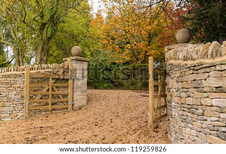 Stylish wooden gates across gravel drive and cotswold stone wall - stock photo