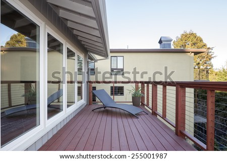 Stylish wooden outdoor terrace with ergonomic comfy Outdoor Furniture and Wire Fence.