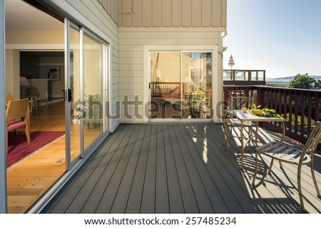 Stylish wooden outdoor terrace with seating arrangement in wooden teak outdoor furniture and wooden fence with french sliding glass doors.