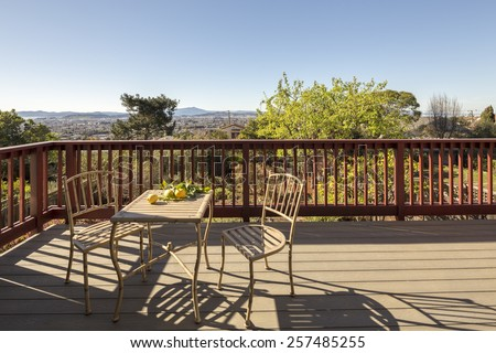 Stylish wooden outdoor terrace with seating arrangement in wooden teak outdoor furniture and wooden fence.