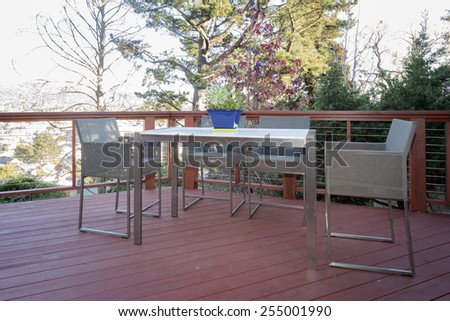 Stylish wooden outdoor terrace with seating arrangement, outdoor furniture and wire fence.