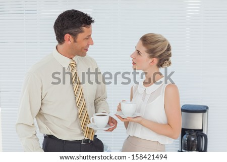 Stylish workmates having coffee together in break room