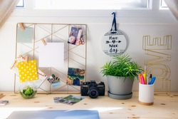 Stylish workplace at home. Wooden desk with closed laptop, moodboard with pined mockup white notes and photos, vintage photo camera, green plants. Sunny day. Summer mood workspace. Vacation memories.